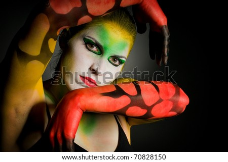 lowkey bodypainting with high contrast in colour yellow red and green - stock photo