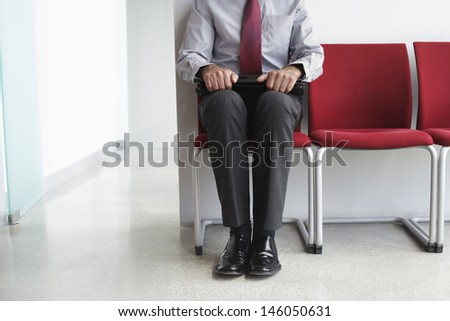 Lowsection of a male executive sitting with laptop on chair in corridor - stock photo