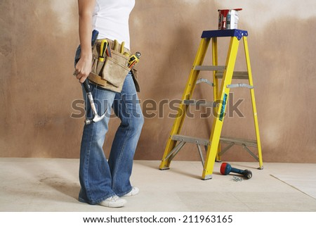 Lowsection of a woman with toolbelt and hammer leaning against wall - stock photo