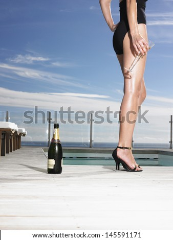 Lowsection of a young woman in bathing suit holding champagne glass at poolside - stock photo
