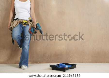 Lowsection of a young woman with toolbelt and drill leaning against wall - stock photo