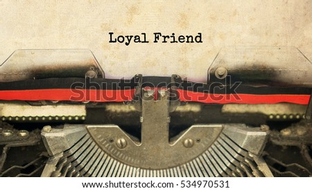 loyal friend typed words on a vintage typewriter with vintage background