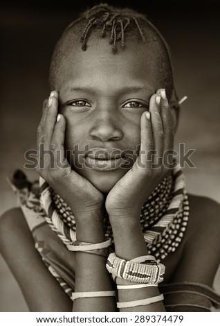 LOYANGALANI - KENYA - JANUARY 26, 2015: Unidentified young Turkana girl with traditional headdress on January 26, 2015 in Loyangalani, Kenya. - stock photo