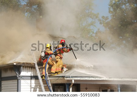Lt Martin and FF Sullivan performing horizontal ventilation on a Single family dwelling on fire on SE Mill Street in the Mill Pine Historic District of Roseburg Oregon. - stock photo
