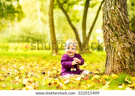 Lttle girl near a tree in the park - stock photo