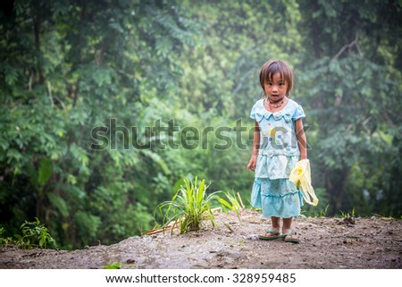 LUANG PRABANG, LAO - Aug 01, 2015: Unidentified kids in LUANG PRABANG , Laos Portrait of Hmong little girl child on July 01, 2015. Children play he was standing on a hill. - stock photo