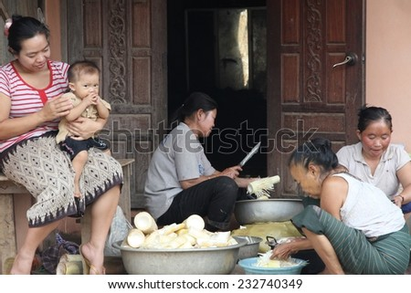 LUANG PRABANG, LAOS - AUGUST 16: A group of hill tribe women sitting on a house doorstep shredding bamboo in the countryside of Luang Prabang, Laos on the 16th August, 2014.