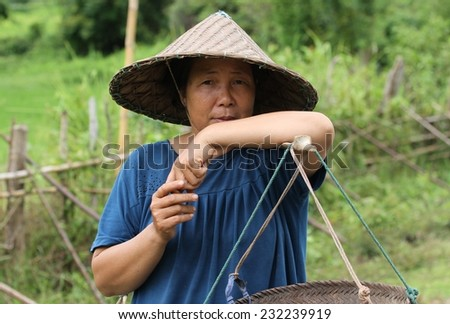 LUANG PRABANG, LAOS - AUGUST 16: A local peasant woman carrying baskets over her shoulders on a countryside road near Luang Prabang, Laos on the 16th August, 2014.