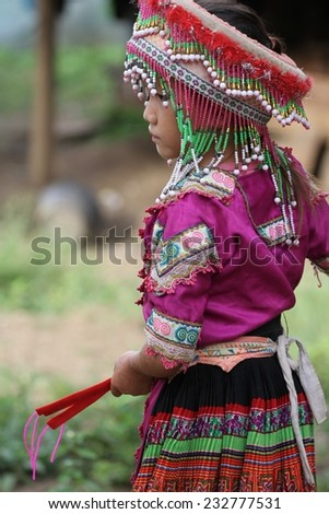 LUANG PRABANG, LAOS - AUGUST 16: A young girl in traditional Hmong hill tribe dress with elaborate head wear near Luang Prabang, Laos on the 16th August, 2014.