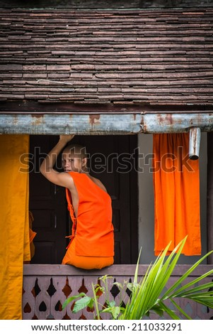 LUANG PRABANG, LAOS - August 11: Unidentified monk in Wat Xieng Thong pagoda on August 11, 2014, in Luang Prabang, Laos. About 60% of the population of Laos practice Theravada Buddhism. - stock photo