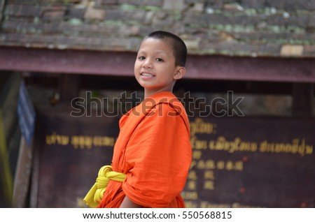 LUANG PRABANG, LAOS - JANUARY 5, 2017: The buddhist students in Luang Prabang on the way to buddhist temple school for learning how to b a good monk, Laos