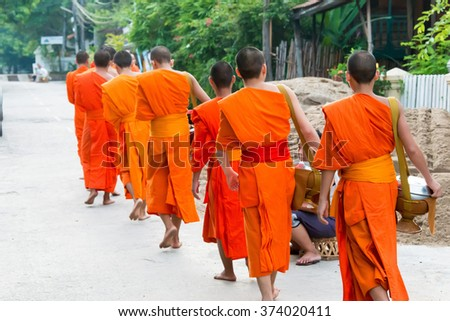 Luang Prabang, Laos - Jun 13 2015: Buddhist alms giving ceremony in the morning. The tradition of giving alms to monks in Luang Prabang has been extended to tourists.