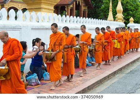 Luang Prabang, Laos - Jun 14 2015: Buddhist alms giving ceremony in the morning. The tradition of giving alms to monks in Luang Prabang has been extended to tourists.