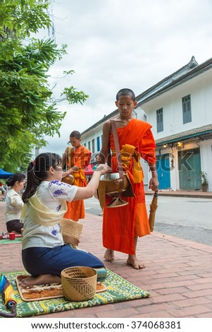 Luang Prabang, Laos - Jun 15 2015: Buddhist alms giving ceremony in the morning. The tradition of giving alms to monks in Luang Prabang has been extended to tourists.