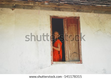 LUANG PRABANG, LAOS - SEPTEMBER 5: Unidentified monk in Wat Xieng Thong pagoda on September 5, 2011, in Luang Prabang, Laos. About 60% of the population of Laos practice Theravada Buddhism. - stock photo