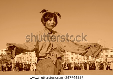 LUANNAN COUNTY - FEBRUARY 10: Buffoon wearing colorful clothes, performing yangko dance in the street, during the Chinese Lunar New Year, February 10, 2014, Luannan County, Hebei Province, China. - stock photo