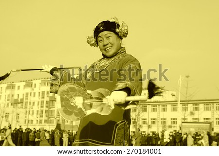 LUANNAN COUNTY - FEBRUARY 11: Buffoon wearing colorful clothes, performing yangko dance in the street, during the Chinese Lunar New Year, February 11, 2014, Luannan County, Hebei Province, China.   - stock photo