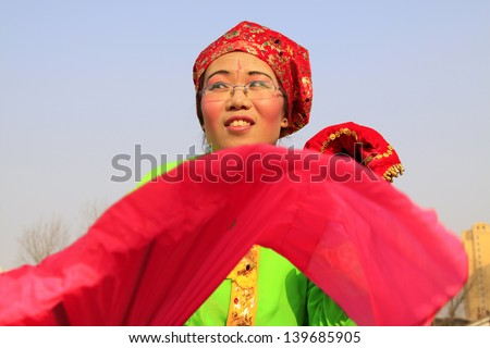 LUANNAN COUNTY - FEBRUARY 23: During the Chinese Lunar New Year, people wear colorful clothes, yangko dance performances in the streets, on February 23, 2013, Luannan County, Hebei Province, China.