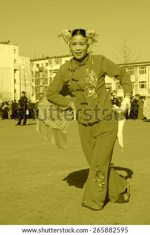 LUANNAN COUNTY - FEBRUARY 10: Lady wearing colorful clothes, performing yangko dance in the street, during the Chinese Lunar New Year, February 10, 2014, Luannan County, Hebei Province, China.  - stock photo