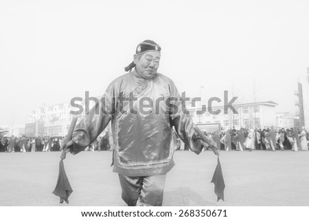 LUANNAN COUNTY - FEBRUARY 12: Old man holding pairs of wooden stick performing yangko dance in the street, during the Chinese Lunar New Year, February 12, 2014, Luannan County, Hebei Province, China. - stock photo