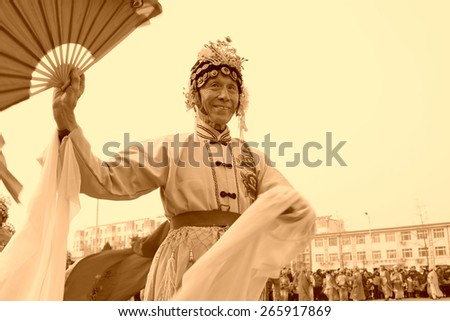 LUANNAN COUNTY - FEBRUARY 15: Old man wearing colorful clothes, performing yangko dance in the street, during the Chinese Lunar New Year, February 15, 2014, Luannan County, Hebei Province, China. - stock photo