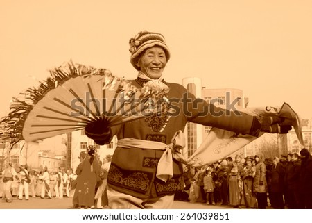 LUANNAN COUNTY - FEBRUARY 12: Woman wearing colorful clothes, performing yangko dance in the street, during the Chinese Lunar New Year, February 12, 2014, Luannan County, Hebei Province, China.  - stock photo
