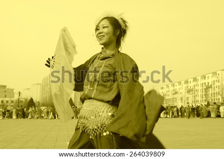 LUANNAN COUNTY - FEBRUARY 13: Young woman wearing colorful clothes, performing yangko dance in the street, during the Chinese Lunar New Year, February 13, 2014, Luannan County, Hebei Province, China. - stock photo