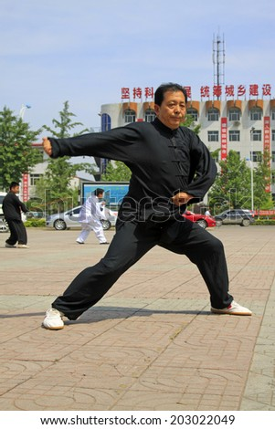 LUANNAN COUNTY - JUNE 29: man in black was performing shadowboxing in the square, on june 29, 2014, LuanNan county, hebei province, China