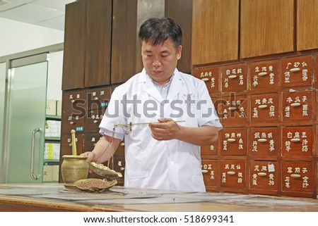 Luannan County - June 18th: a pharmacist weighing Chinese medicinal herbs, June 18th, 2015, Luannan County, Hebei Province, China