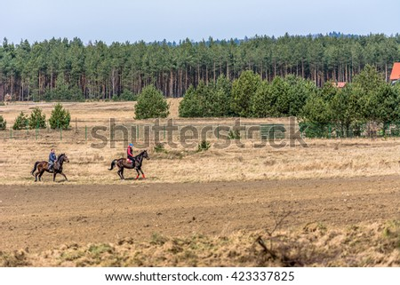 LUBOWIDZ, POLAND - APRIL 3, 2016: Two people on a horse ride through rural fields