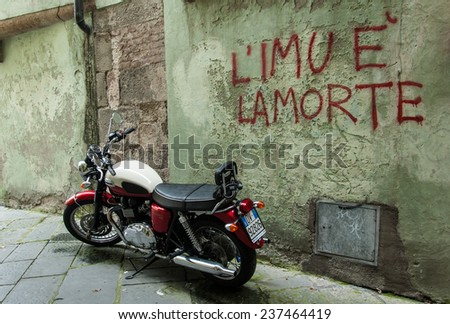 """Lucca, Italy, August 5 2014: Old motorcycle standing in front of wall with writing """"L'IMU è la morte"""". Refers to an unpopular tax on property (called IMU) that has been introduced by the government. - stock photo"""