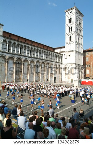 Lucca, Italy, 18 July 2006: Marching band and cheerleaders on the square of San Michele with the cathedral of Lucca on Italy