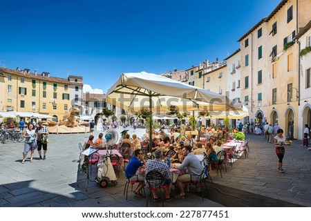 LUCCA, Italy 30 June 2014 people sitting outside at the restaurant on of Piazza Dell Anfiteatro, 30 June 2014 Lucca, Tuscany, Italy, Editorial for only  - stock photo