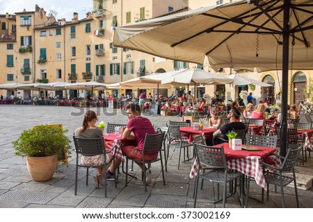 Lucca, Italy - September 14, 2015: Unidentified people eating traditional italian food in outdoor restaurant in city center of Lucca, Italy. - stock photo