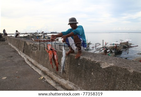 LUCENA CITY, PHILIPPINES - APRIL 19: Unidentified fisherman sells his catch April 19, 2010 at Dalahican port, Lucena City, Philippines. Fishing remains one of the source of livelihood among Filipinos. - stock photo
