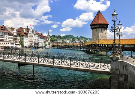 Lucerne is with the Chapel Bridge and water tower a historic and very famous town in Switzerland. It is visited from people around the world. - stock photo