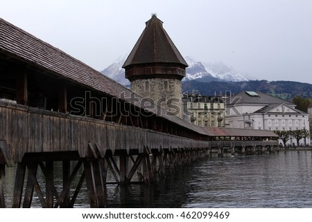 LUCERNE, SWITZERLAND -April 13,2016: view on the Reuss river with the Chapel Bridge,the city's symbol and one of the Switzerland's main tourist attractions on a rainy day .Lucerne, Switzerland.