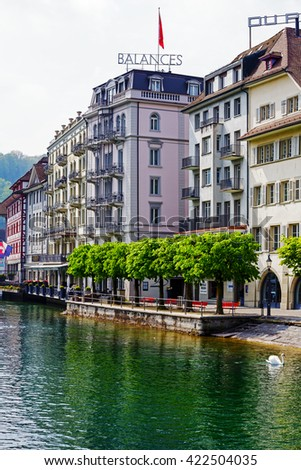 LUCERNE, SWITZERLAND - MAY 02, 2016: Colorful  buildings along the river shows unique character of the Old Town and it looks to be tuned with modern times and offers variety of sightseeing attractions - stock photo