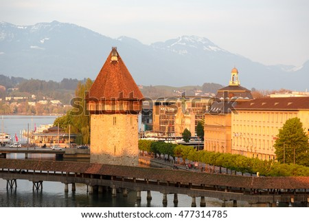 LUCERNE, SWITZERLAND - MAY 02, 2016: Evening view towards the octagonal tower that was built in the river Reuss and is located next to the roofed Chapel Bridge that are the most famous city landmark