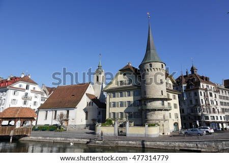 LUCERNE, SWITZERLAND - MAY 05, 2016: Haus zur Gilgen, one of the oldest stone houses in the city and St. Peter Chapel, both buildings are located on the right bank of river Reuss