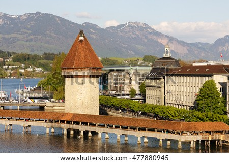 LUCERNE, SWITZERLAND - MAY 04, 2016: Landscape of the city including its most recognizable landmarks. Octagonal tower that was built in the river Reuss and the roofed Chapel Bridge can be seen.