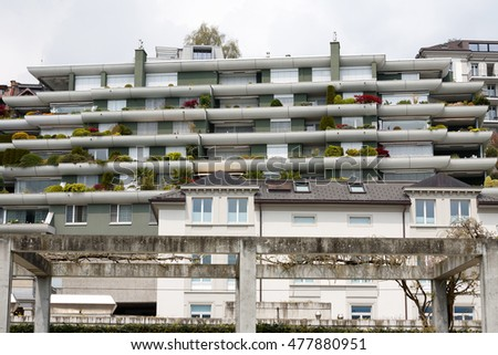 LUCERNE, SWITZERLAND - MAY 03, 2016: Modern facade of apartment building that was built with terraces on which cultivated plants can be seen and the greenery gives the impression of a garden on a wall