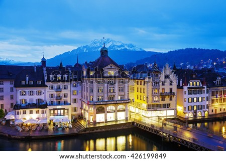 LUCERNE, SWITZERLAND - MAY 03, 2016: Night view towards buildings along the river Reuss shows unique character of Old Town and it looks to be very attractive for tourists visiting the city - stock photo