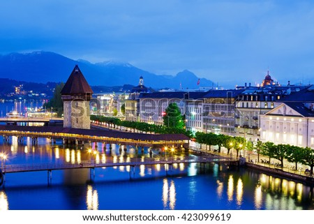 LUCERNE, SWITZERLAND - MAY 03, 2016: Night view towards Chapel Bridge (Kapellbruecke) together with the octagonal tall tower (Wasserturm) it is one of the Lucerne's most famous tourists attraction  - stock photo