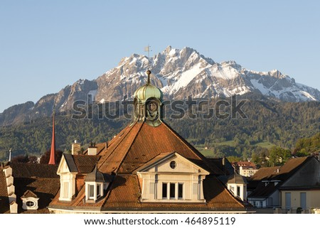 LUCERNE, SWITZERLAND - MAY 06, 2016: Sloping roof covered with tiles of a historic building shows a proximity of the city to the snowy peak of Pilatus, one of the most well-known peaks in Switzerland