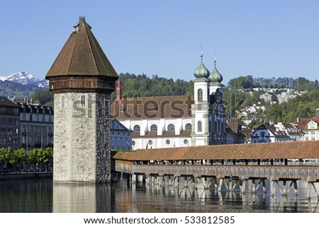 LUCERNE, SWITZERLAND - MAY 05, 2016: Three of most recognizable landmarks in the city are the octagonal tower and roofed Chapel Bridge and the Jesuit Church