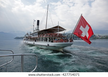 LUCERNE, SWITZERLAND - MAY 03, 2016: Uri vessel departs from Ferry Terminal Verkehrshaus-Lido. It is  the oldest operating Swiss paddle wheel steamer and was built in 1901 - stock photo
