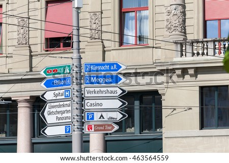 LUCERNE, SWITZERLAND - MAY 04, 2016: Various types of signposts that indicates diverse travel destinations in two different directions are installed on a pole in the center of town