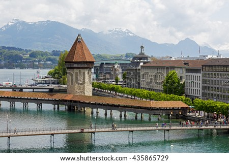 LUCERNE, SWITZERLAND - MAY 04, 2016: View towards Chapel Bridge together with the octagonal tall tower it is one of the Lucerne's most famous tourists attraction  - stock photo