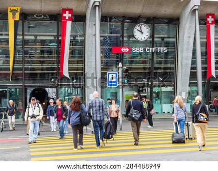 LUCERNE, SWITZERLAND - SEP 16, 2014: People crossing the road in front of Lucerne central train station. Lucerne is the capital of the Canton of Lucerne and the capital of the Lucerne district. - stock photo